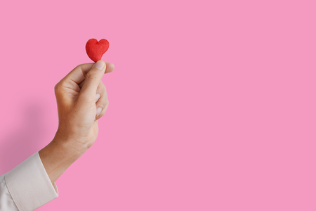 finger shape: Mans hand holding and showing heart shape, love concept, give love, or valentines day season. Pink background. Stock Photo
