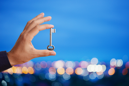 Business man's hand holding and raising key on abstract twilight bokeh night scene background, blank space for your text and design. Business concept of key to success. Standard-Bild
