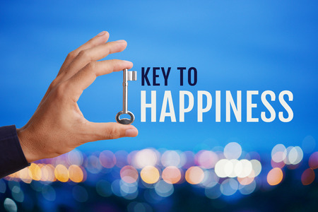 Business man's hand holding and raising key with word Key to HAPPINESS on abstract twilight bokeh night scene background, blank space for your text and design. Business concept of key to success. Stockfoto