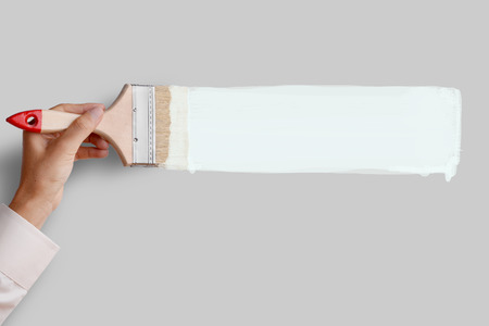 advertising space: Mans hand holding paintbrush paint white color on gray color wall, blank space for your text, banner, copyspace, advertising, or your design. Stock Photo