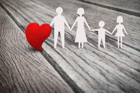 single father: Single red heart shape on rustic wood panel with family paper character, abstract background in love in family, father, mather, son, daughter concept. Retro and vintage style.