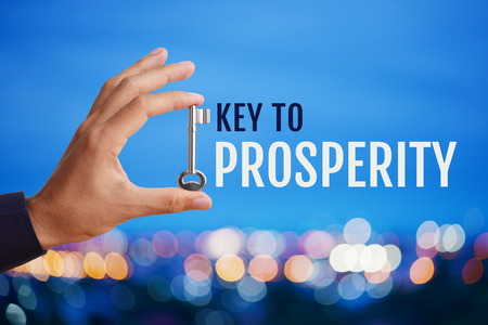 prosperidad: Business mans hand holding and raising key with word Key to PROSPERITY on abstract twilight bokeh night scene background. Business concept of key to prosperity.