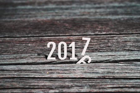 replace: Happy New Year 2017, coming to replace 2016. Abstract background for new year 2017 celebration, alphabet number paper character on grunge retro wood panel background, vintage style. Stock Photo