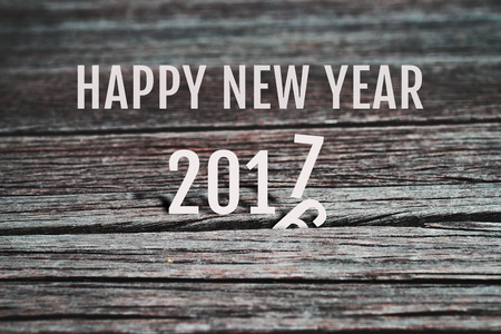 replace: Celebrate Happy New Year 2017, coming to replace 2016. Abstract background for new year 2017 celebration, alphabet number paper character on grunge retro wood panel background, vintage style.