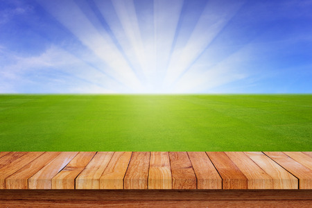blue ray: Nature backrground of green grass field, blue sky, white cloud, ray of sunshine, with wood floor, glowing light effect. Stock Photo