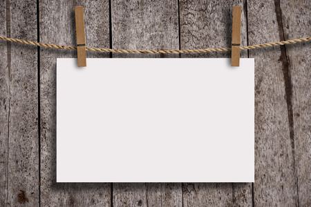 vintage document: Blank white paper with wood clip on wood wall panels, grunge wood background. Blank paper for your text, copyspace or your design. Stock Photo
