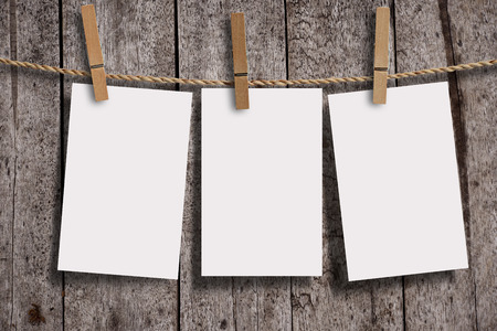 Blank three page of white paper with wood clip on wood wall panels, grunge wood background. Blank paper for your text, copyspace or your design.