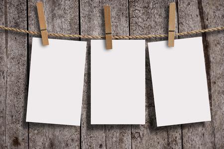 Blank tre pagine di carta bianca con clip in legno sui pannelli di parete di legno, sfondo di legno grunge. Carta vuota per il tuo testo, copyspace o il tuo design.