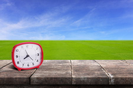 Clock tell time at nearly 8 oclock on grunge wood table or floor panel, in front of green grass field with blue sky background. Stock Photo