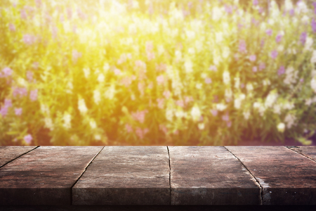 blur effect: Grunge vintage wood panel table in front of glowing beautiful sunlight in autumn with blur effect flower garden. Stock Photo