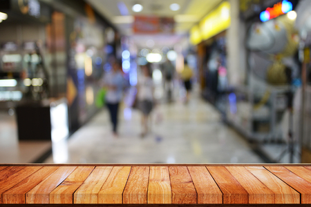store front: Wood panel table background in front of blur effect of people walking and go shopping in department store.