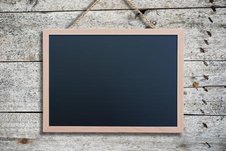 pizarron: Pizarra que cuelga en el fondo de madera del panel de la pared de la vendimia del grunge. Espacio vacío y en blanco para su texto, copyspace o diseño.