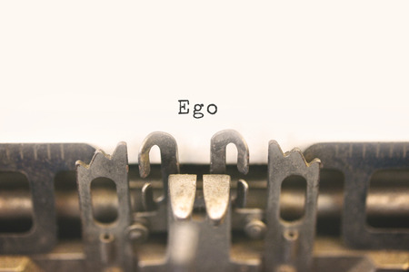 ego: Close up of antique typewriter with text Ego on white paper. Selective focus on message, vintage filter style. Stock Photo