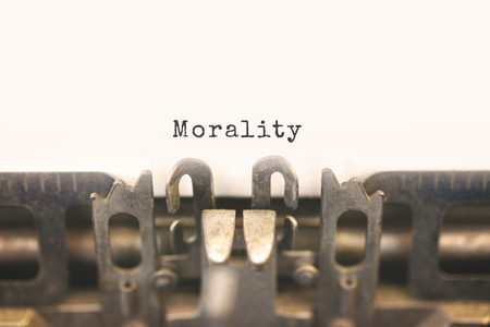 morality: Close up of antique typewriter with text Morality on white paper. Selective focus on message, vintage filter style.