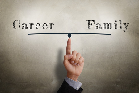 wall background: Businessman hand point at balance between  Career and Family. Glow light efffect, vignette and shadow on concrete wall background. Stock Photo