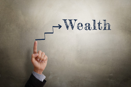 business direction: Businessman hand point at sketching arrow in direction to text Wealth, business concept of being wealthy. Glow light effect, vignette and shadow on concrete wall background.