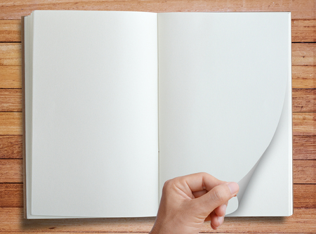 notebook page: Hand pick and open page of notebook isolated on wood desk background, top view. Stock Photo