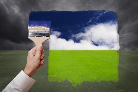 La mano del hombre sosteniendo un cepillo de pintura, pintura brillante día con el cielo azul y la nube blanca en campo de hierba verde sustituir mal día nublado con tormenta de lluvia. Ilustración conceptual del nuevo mundo mejor, mejor día o visión optimista.