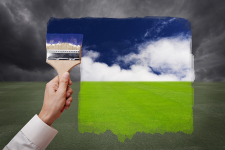 Man hand holding painting brush, paint bright day with blue sky and white cloud on green grass field replace bad cloudy day with storm rain. Conceptual illustration of new better world, better day or optimistic vision. Stock Photo