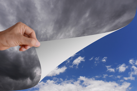 blue sky thinking: Hand pick and pull paper or cutain from bad cloudy sky to be clear bright blue sky and white cloud. Conceptual illustration of optimistic idea, change, opportunity, or better step.
