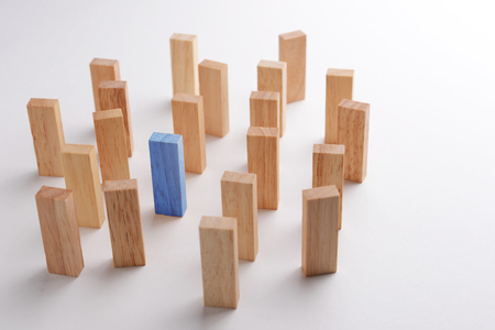 differentiate: One blue wood block outstanding and different in crowd, metaphor to business concept of being differentiate, individual, leadership, or outstanding. Selective focus, gray background. Stock Photo