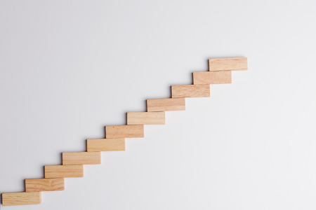 raising: Wood block raising up in growing  statistics graph shape, top view on gray desk background with copy space. Business concept in growth economy. Stock Photo