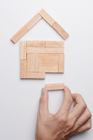 Man Hand holen letzte Stück Holz-Block-Haus-Modell vervollständigen, Ansicht von oben auf grauem Hintergrund.