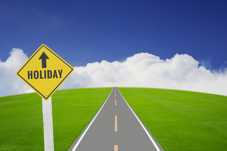 go ahead: Traffic plate with text HOLIDAY by long road on green grass field and blue sky, white cloud background. Business concept in holidays is along way to go ahead.