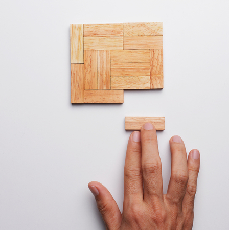 fingers put together: Man hand push last piece of wood block to complete the unity, metaphor to key to success. Top view, gray background.