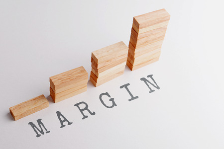 margins: Stack of wood block in statistics graph shape with text MARGIN. Business concept in rising and growing margins. Selective focus, gray background.
