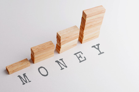 growing money: Stack of wood block in statistics graph shape with text MONEY. Business concept in rising and growing money. Selective focus, gray background. Stock Photo