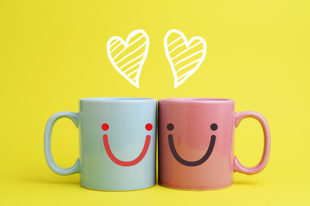 Two blue and pink coffee cup put next to each other with sketching of heart shape, and smiley face expression, in romantic concept. Side view.  Stock Photo