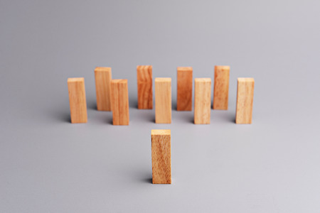 initiatives: One wood block standing in front of group of wood block which standing in line or row, metaphor to leader stand in front of many follower. Business concept in leadership. Selective focus, gray background.