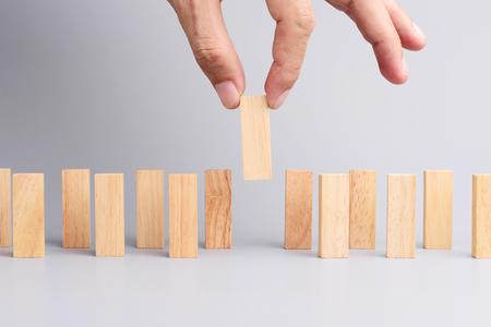 Man Hand holen ein Holzblock aus vielen Holzblock in der Reihe, Metapher Konzept Geschäft in ideale Person wählen Sie aus vielen Kandidaten. Grauer Hintergrund, der Seitenansicht.