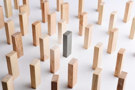 Schwarze Farbe Holzblock heben sich von der Masse ab, Metapher Business-Konzept der individuellen, einzigartigen, hervorragend. Selektiver Fokus, grauen Hintergrund.