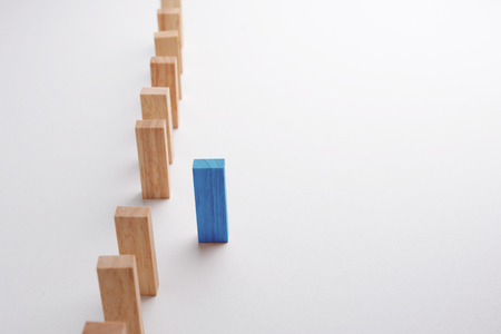 initiative: Blue wood block step forward from other block which queing in line or row, business concept in thinking different, unique, individual, initiative, or leadership. Selective focus on blue wood, gray background.
