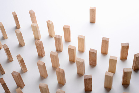 initiatives: One wood block standing in front of group of wood block metaphor to leader stand in front of many follower. Business concept in leadership. Selective focus, gray background.
