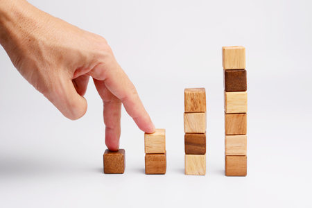 finger shape: Man finger step up on square wood block in shape of  business graph, metaphor to moving up, growing, rising.  Stock Photo
