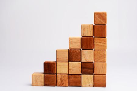 Pila de bloque de madera de forma cuadrada estadísticas gráfico, metáfora de negocio siga creciendo y subiendo. El espacio vacío y espacio en blanco para el texto, diseño o copyspace.