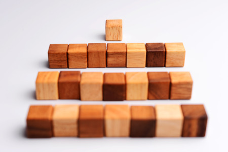 One wood block standing in front of group of cube wood block which standing in line or row, metaphor to leader stand in front of many follower. Business concept in leadership. Selective focus, gray background.