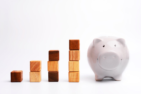 money concept: Stack of wood block in rising financial graph with fat piggy bank, metaphor to business concept in growth, wealth, saving money, financial rising, growing business.