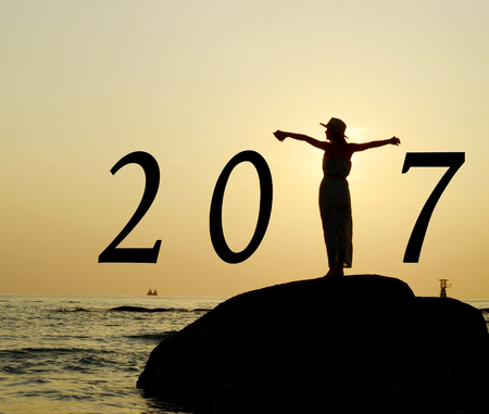 strecthing: Beautiful asian woman standing, streching hands, on stone silhouetted the sunrise in morning scene with year 2017 calendar.