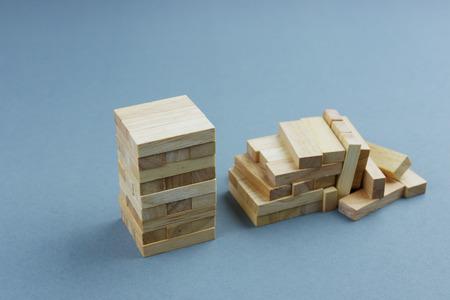Estable torre de bloques de madera de pie contra el colapso uno, metáfora para la comparación de la supervivencia del negocio a otra quiebra o destrucción.
