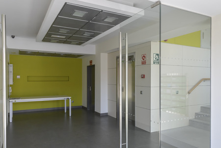 Offices hall with glass, ceramic floor an white and green walls photo