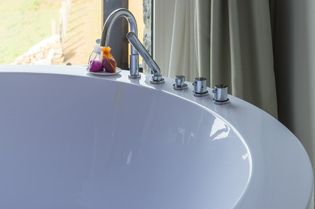 Detail of a white round bath with little bottles of gel photo