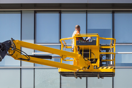 Workers on a lifting crane repairing a curtain wall Stockfoto