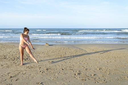 oliva: Young caucasian woman doing cartwheel on the beach Stock Photo
