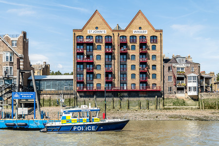 st john: LONDON, UK - AUGUST 22, 2015: Housing in London riverside at St John Wharf and police boat moored
