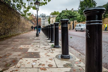 LONDON, UK - AUGUST 24, 2015: Row of bollards in a street of London, low angle view on a cloudy day