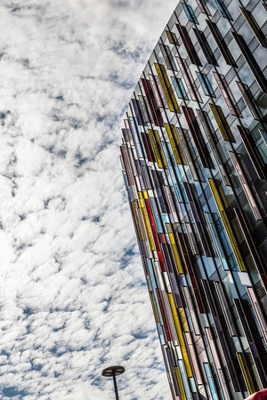 low angle view: London, UK - August 19, 2015: Modern office building in London with a colorful facade of glass. Low angle view